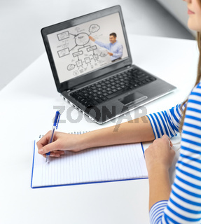 student girl with exercise book, pen and laptop
