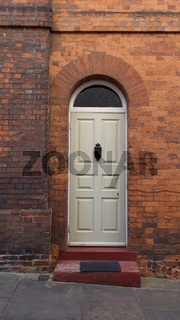 Old English Georgian door set in red brick house with step in front