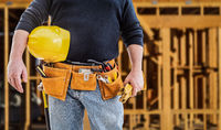 Contractor With Tool Belt and Hard Hat In Front of Wood Framing Construction Site
