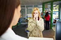 Frau mit Schnupfen in Apotheke