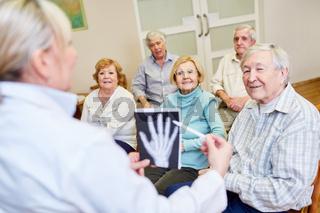 Ärztin macht einen Gesundheitskurs für Senioren im Altenheim oder Seniorenheim