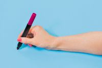 Woman holding pencil on blue background
