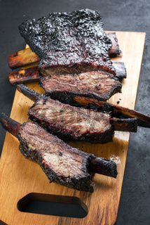 Barbecue burnt chuck beef ribs marinated and sliced as top view on a modern design wooden board