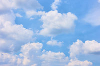 Pastel blue sky with white heap clouds