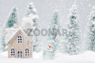 Snowman and house in winter