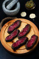 Pepper steaks on wooden cutting board