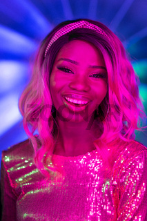 Charming African woman toothy smiles in neon glow. Dark skinned girl with ombre hairstyle in glittering dress smiling broadly while looking at camera in fluorescent pink light. Close up portrait