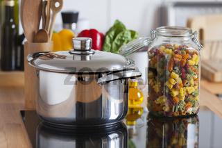 Grosser Kochtopf und Glas mit bunten Nudeln