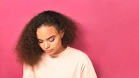 Beautiful but sad African American young girl looking down lowered head wearing peachy t-shirt isolated on pink background. Beauty concept