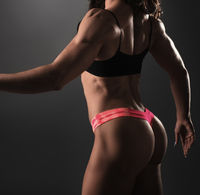 Back view of female bodybuilder posing in studio