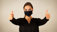 Positive woman wearing black face mask showing her thumbs up
