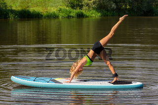 Young caucasian woman exercises yoga on SUP