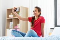 happy girl with smartphone taking selfie at home