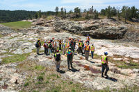 SUDBURY, ONTARIO, CANADA - MAY 21 2009: Group of workers and geologists in hardhats and high-visibility vests standing on geological outcrop site.