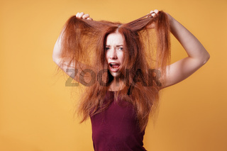 frustrated young woman pulling and tearing her hair