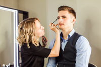 Professional actor preparation before shoot. Handsome young man applying by professional make up of visagist.