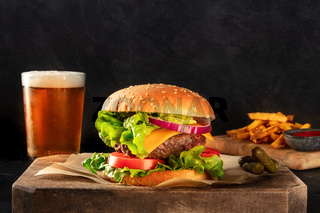 Beef burger with beer and French fries, side view on a dark background