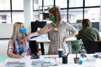 Two diverse businesswomen wearing face masks bumping elbows in creative office