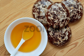 Honey in a white cup and chocolate gingerbread on a wooden background