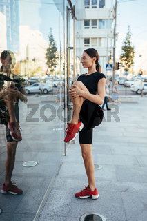 Young beautiful girl doing stretching in front of a modern building