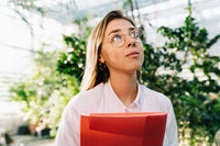 Young agricultural engineer working in greenhouse. Young female scientist looks away