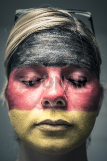 Woman with flag of Germany on face and closed eyes