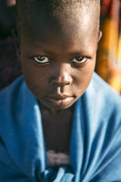 BOYA TRIBE, SOUTH SUDAN - MARCH 10, 2020: Child wrapped in blue cloth looking at camera while living in Boya Tribe village in South Sudan, Africa