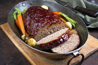 Traditional American meatloaf with ketchup from ground beef with carrots and onion as closeup in a copper saucepan