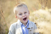 Funny cheerful little boy with blond hair smiles and looks into the camera.