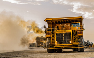 Mining dump trucks transporting Platinum ore for processing