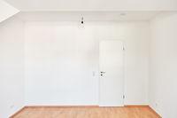 Leerer Raum mit weißen Wänden und geschlossener Tür
