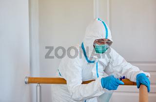Putzkraft in Schutzkleidung desinfiziert Treppengeländer in Pflegeheim oder Klinik