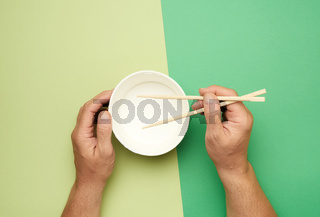 Pair of wooden chopsticks in a male hand and empty paper plate