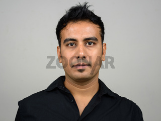 Portrait of handsome Indian businessman against white background