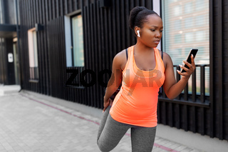 african woman with smartphone exercising outdoors