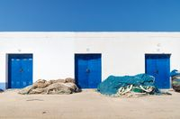 Harbour warehouse building with blue doors and fisher nets, Altea, Costa Blanca, Spain