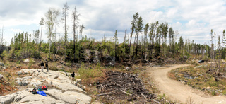 SUDBURY, ONTARIO, CANADA - MAY 23 2009: Group of workers and geologists standing and working on geological outcrop site.