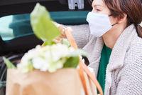Frau mit Mundschutz trägt Tasche mit Blumen aus Auto Kofferraum