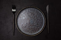 Trendy dark dishes on dark background, top view