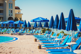 blue umbrellas and sun beds near the pool in the summer resort.