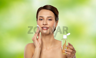 young woman with toner or cleanser and cotton pad