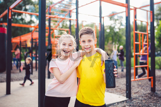 Sportive friends. Brother and sister standing together at street city gym. Children athletes hug smile during workout training. Twins boy and girl posing on playground. Physical development education