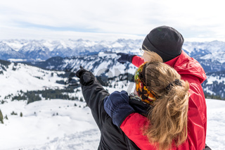 Senior couple is hiking in alpine snow winter mountains enjoying panorama view and pointing with finger to mountain peaks. Allgau, Bavaria, Germany.