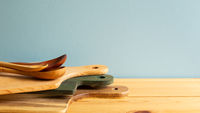 Wooden tray, cutting board, plate and spoons on wooden table with blue background