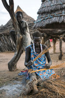 TOPOSA TRIBE, SOUTH SUDAN - MARCH 12, 2020: Woman sitting on dirty ground near hut and kid and weaving product from straw in village of Toposa Tribe in South Sudan, Africa