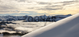 Snow covered mountains with inversion valley fog and trees shrouded in mist. Scenic snowy winter landscape panorama in Alps at sunset. Allgau, Kleinwalsertal, Bavaria, Germany.