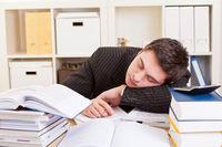 Mann schläft am Schreibtisch