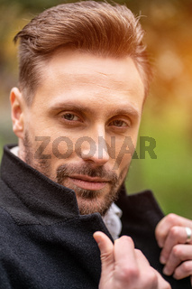 Handsome man holding a corner of his coat standing on the street in an autumn coat smiling looking at the camera. Handsome young man in dark blue coat and scarf or muffler