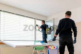 professional cleaning team in an apartment cleaning windows and blinds with a vacuum and other cleaning equipment