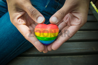 Decorative Heart with rainbow stripes in female hands. LGBT pride flag, symbol of lesbian, gay, bisexual, transgender for social movements. Homosexual love, Human rights concept. Copy space.